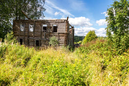 Abandoned and destruction old rural wooden house in russian village in summer sunny day Stock Photo