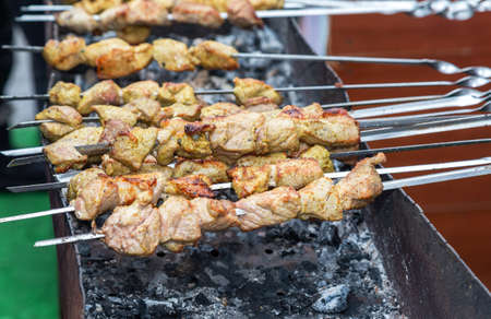 Grilled appetizing kebab cooking on metal skewers. Shashlik during of cooking on the mangal over hot charcoals outdoors, street food