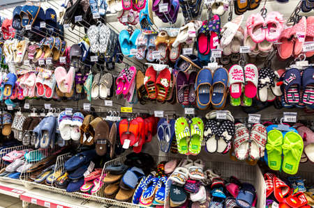 Samara, Russia - March 31, 2019: Various colorful slippers selling at the showcase in chain hypermarket Editorial