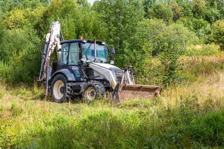 Novgorod, Russia - August 14, 2020: Bulldozer working at the countryside in summer day