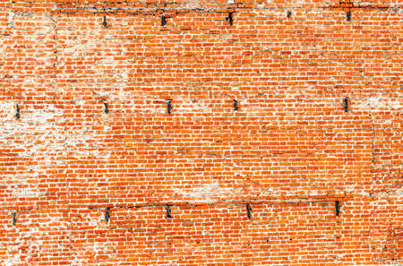 Red brick wall of medieval Kolomna Kremlin as background texture. Weathered cracked brick wall