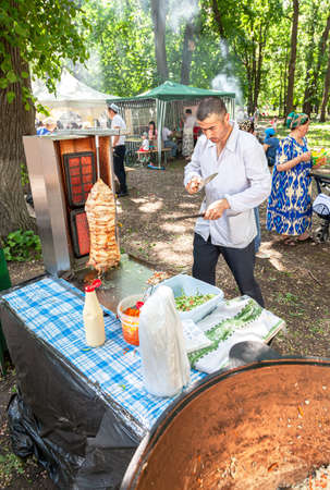 Samara, Russia - May 28, 2016: Cooking traditional fast food doner kebab meat on a rotary grill. Shawarma is one of the most popular fast food