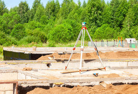 Geodetic equipment optical level mounted on tripod at the construction site. Surveyors ensure precise measurements