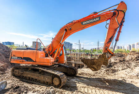 Samara, Russia - May 6, 2021: Backhoe working on the construction of new road in summer day. Heavy machinery at the construction site