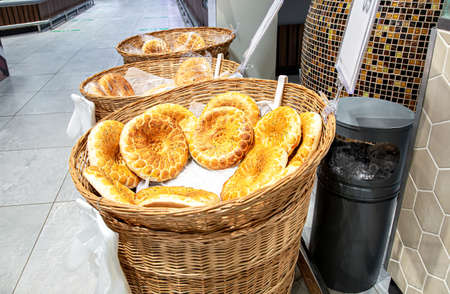 Traditional appetizing uzbek flatbreads with sesame seeds from the tandir selling at the store