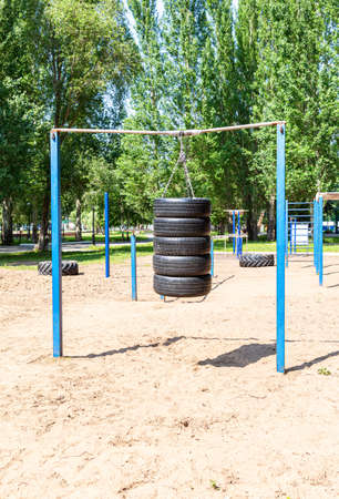 Car tires for sports training are suspended on chains on the sports ground Standard-Bild