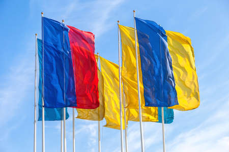 Various colorful flags waving in the wind against the blue sky background Standard-Bild