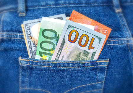 Various banknotes of Euro and american currency sticking out of the jeans pocket. Money in jeans pocket for travel and shopping