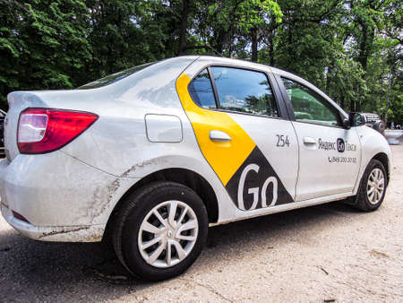 Samara, Russia - June 5, 2021: Yandex Go taxi cab is parked on a city street in summer