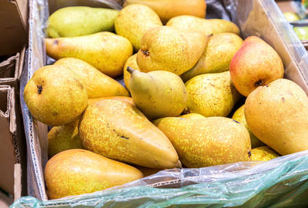 Fresh pears of new harvest in the cardboard box at the grocery store