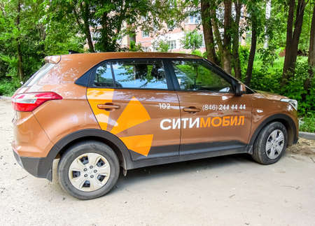 Samara, Russia - June 10, 2021: Citymobil taxi is parked on a city street in summer. Text in Russian: Citymobil