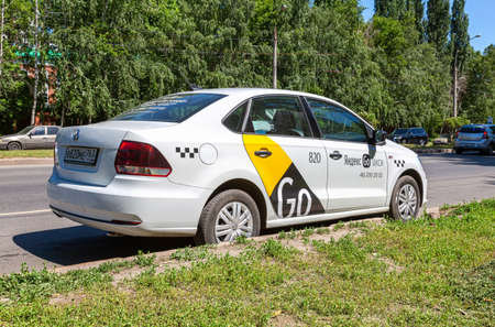 Samara, Russia - June 18, 2021: Yandex Go taxi cab is parked on a city street in summer