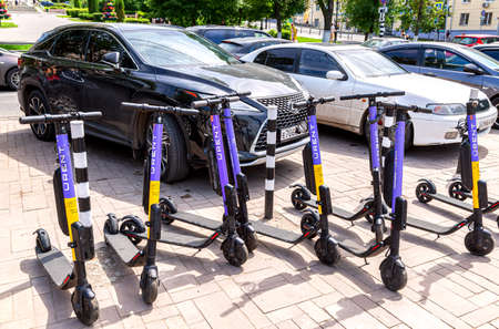 Samara, Russia - June 14, 2021: Cars and electric scooters for rental at the city street. Improve sustainable mobility in the city Editorial