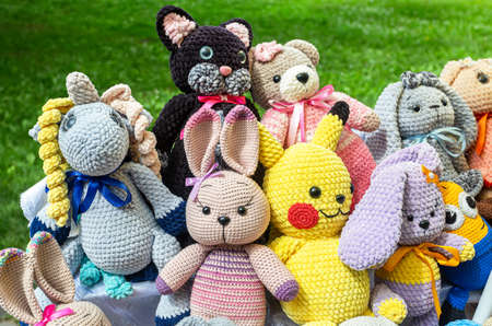 Samara, Russia - June 13, 2021: Various knitted soft toys outdoors in city park Editorial