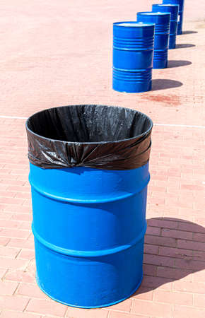 Metal barrel with plastic bag for waste at the city pavement Standard-Bild