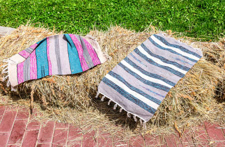 Handmade striped rugs lie on the hay in sunny day Standard-Bild