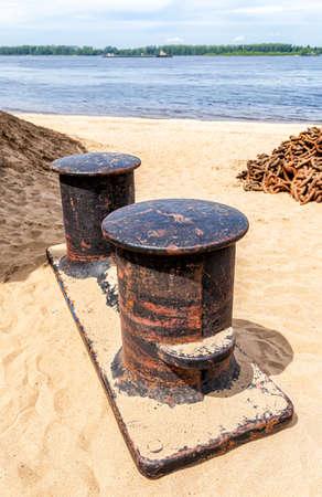 Old rusty mooring bollard in the harbor on the sand beach Standard-Bild