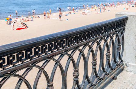 Cast iron trellis on the embankment against the background of a sandy beach with people having a rest in summer