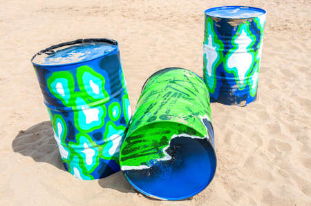 Samara, Russia - June 14, 2021: Painted metal barrels lie on the sand on a sunny day. Barrels are painted in different colors