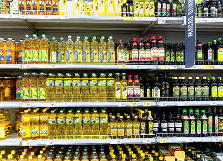 Samara, Russia - June 19, 2021: Assorted sunflower and olive oils in bottles ready for sale in the superstore. Bottled sunflower, olive oils as background