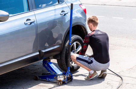 Samara, Russia - July 4, 2021: Mechanic is repairing vehicle. Repairman is removing wheel by electric wrench, tire mounting equipment at the outdoors. Man repair the car. Tire fitting concept