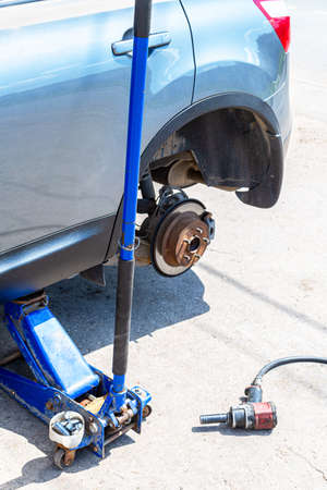 Car at the tire mounting with removed wheel on pneumatic jack. Seasonal tire change. Car service concep Standard-Bild