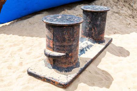 Old rusty mooring bollard at the harbor on the sand beach