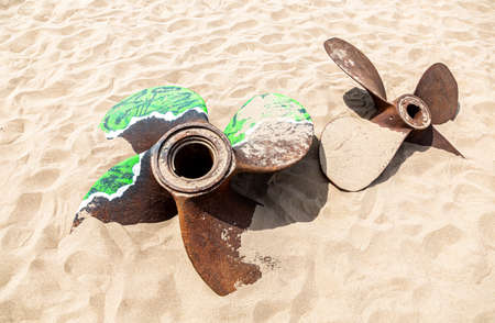 Old rusty ship propellers of a marine ship on the sand