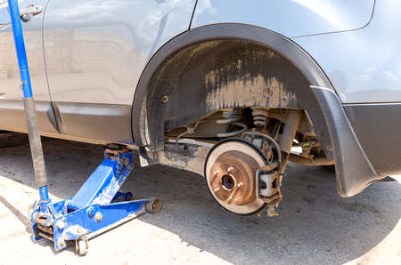 Ð¡ar at the tire mounting with removed wheel on pneumatic jack. Seasonal tire change. Car service concep Standard-Bild