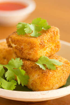 silken: Breaded Fried Silken Tofu w Chili Oil in Background Non sharpen Stock Photo