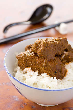 meaty: Chinese Styled Pork Rendang on steamed long grain rice. Non sharpened file Stock Photo