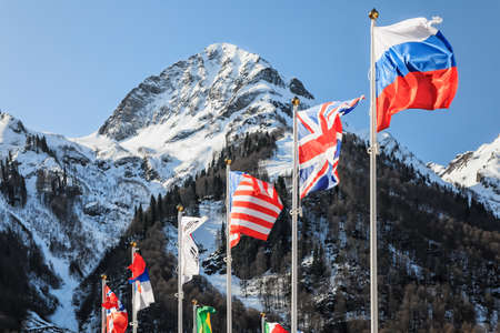 flagpoles: Flags of Russia, UK, USA and other countries waving in the wind as a friendship and collaboration symbol on snowy mountains and blue sky background. Various flattering national flags on flagpoles Stock Photo