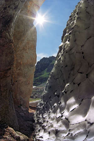 cleft: A cleft in Caucasian mountains (so called rantcluft), when firn thaws out from the rock which gets warm due to the summer sun Stock Photo