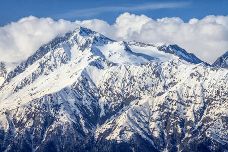 tele up: Beautiful mountain scenic landscape of the Main Caucasian ridge with snowy peak on blue cloudy sky background