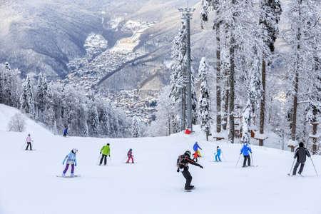 スキーヤーとスノーボーダーが雪に覆われた冬山を背景にソチ マウンテン リゾートにはスキー場に乗って 写真素材
