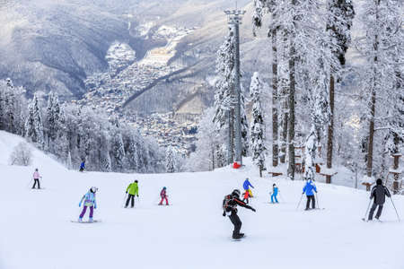 Skiers and snowboarders riding on a ski slope in Sochi mountain resort on snowy winter mountain background