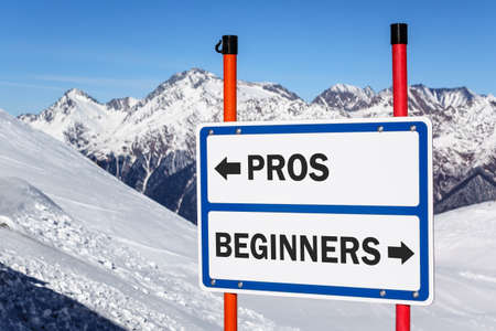 delimit: Pros and beginners direction sign bifurcating ski and snowboard riders streams against snowy mountain and blue sky winter background Stock Photo