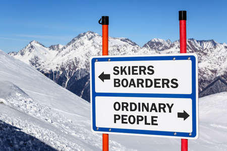 Skiers and boarders versus ordinary people gradation sign bifurcating streams against snowy mountain and blue sky winter background