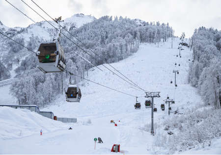 skiers: Sochi, Russia - January 9, 2015: Ski slopes and cableway cabin lifts in Krasnaya Polyana mountain resort can be hosting skiers and snowboard riders right until June Editorial