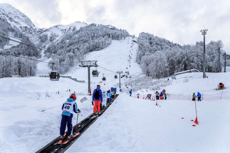 kids at the ski lift: Sochi, Russia - January 9, 2015: Snowy ski slopes and cableway ski lifts in Krasnaya Polyana winter mountain resort can be hosting skiers and snowboarders right until June. Kids ride on a travolator Editorial