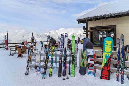 Sochi, Russia - January 9, 2015: Ski and snowboard equipment is resting against a winter cafe fence