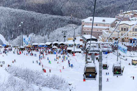 Sochi, Russia - January 9, 2015: Covered with snow ski slopes and cableway lifts in Krasnaya Polyana winter mountain resort can be hosting skiers and snowboard riders during 6 month a year