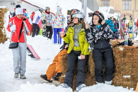 Sochi, Russia - January 9, 2015: Ski slopes in Gorky Gorod winter resort can be hosting skiers and snowboard riders during 6 months a year. Two women are having rest after ski riding Editorial