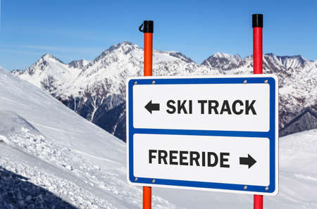 delimit: Ski track and freeride delimitation sign with arrows showing opposite directions against snowy mountain peak and blue sky winter background