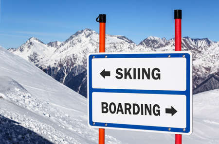 delimit: Skiing and snowboarding delimitation sign with arrows showing opposite directions against snowy mountain peak and blue sky winter background