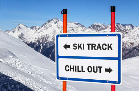 Ski track and chill out dilemma sign with arrows showing opposite directions against snowy mountain peak and blue sky winter background