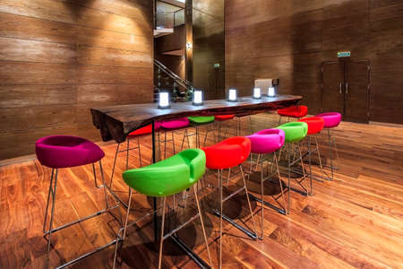 Sochi, Russia - February 26, 2014: View of Gorki Art Hotel lounge wooden interior with modern furniture and comfortable setting. Long wooden dining table with colorful plastic chairs and lit candles