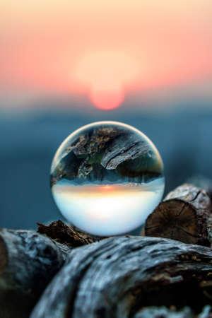 Schilderachtige herfstzonsondergang in de bergen van de Kaukasus bekeken door glazen bol liggend op houtstapel. Verticaal landschap met onscherpe achtergrond Stockfoto