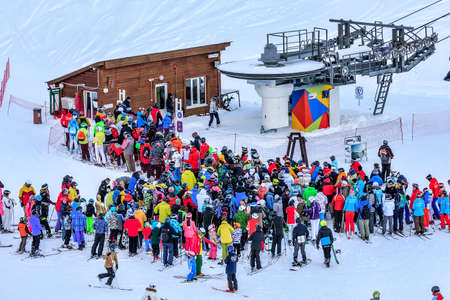 Sochi, Russia - January 7, 2018: Crowds of skiers and snowboarders queue by chair ski lift station of Gorky Gorod mountain ski resort on winter day