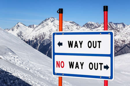 Way out vs no way out information direction sign bifurcating streams at ski resort against snowy mountain peak and blue sky winter background.